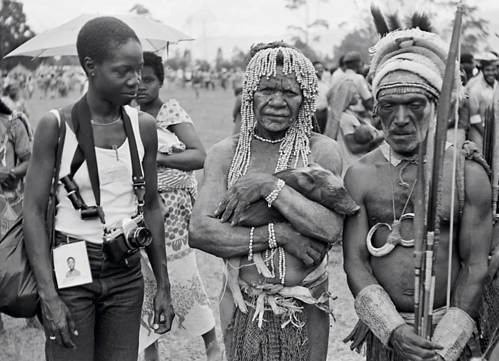 Photo - Group portrait of Merle in a crowded market with two tribespeople, one holding a piglet